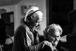 two senior women comforting each other in black & white