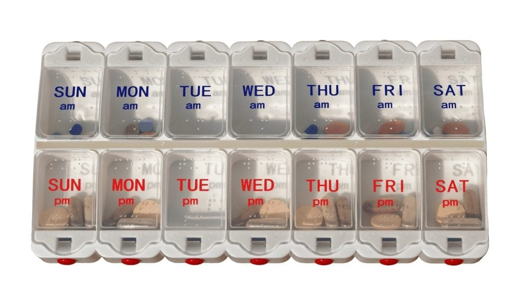 Elderly Medication Management Strategies A plastic pill planner box, with two rows of small containers labeled for each day of the week, the top row for AM and the bottom for PM