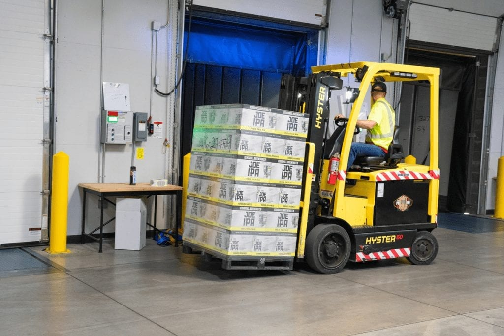 list of workplace accidents and how to prevent them A man backing up a yellow forklift loaded with a pallet of goods, inside a warehouse.